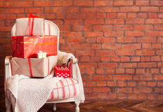 Christmas presents on a wooden floor on a brick wall background. Christmas presents on the armchair on a brick wall background. View with copy space Royalty Free Stock Photography