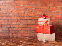 Christmas presents on a wooden floor on a brick wall background. View with copy space Royalty Free Stock Photos