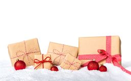 Christmas presents wrapped in brown paper with red ribbon and snow on white background royalty free stock photo