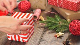 Christmas presents wrapped in eco paper with homemade decoration on wooden background with decor elements.  stock video