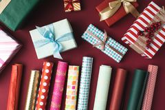 Christmas presents and wrapping papers. Flat lay with arranged colorful  christmas presents and wrapping papers on tabletop Royalty Free Stock Photo