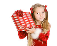 Christmas: Pretty Girl Shakes Gift To Guess What's Inside Stock Photography