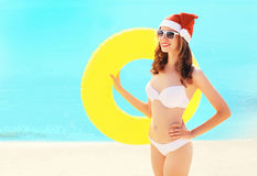 Christmas pretty smiling woman in red santa hat with circle inflatable on beach over blue sea. Background Stock Photo