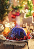 Christmas pudding flambe. On wooden table in rustic Royalty Free Stock Images