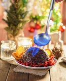 Christmas pudding flambe. On wooden table in rustic Royalty Free Stock Photo