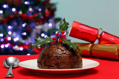 Christmas pudding with holly and crackers Royalty Free Stock Image