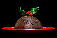 Christmas pudding with holly isolated on black Stock Photos