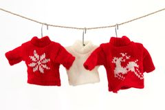 Christmas pullover 2. Three pullovers and a clothesline with a white background Stock Photos