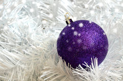 Christmas purple ball on white needless. Christmas purple gleaming ball decoration on white needless with snow flakes Stock Images