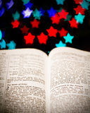 Christmas reading. Focus on Christian Christmas scripture, with star lights in background Royalty Free Stock Photos