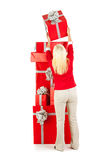 Christmas: Rear View Of Woman Stacking Christmas Presents stock photo