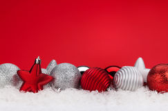 Christmas red background with baubles in snow Royalty Free Stock Photos