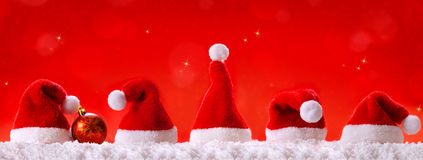 Christmas red background with Christmas hats. Stock Photography