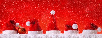 Christmas  red background with Christmas hats. Royalty Free Stock Images
