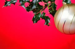 Christmas red background  holly and golden ball Royalty Free Stock Image