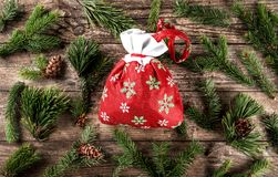 Christmas red bag on wooden background with fir branches and pine cones. Xmas and New Year theme. Flat lay, top view stock photography