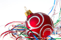 Christmas red ball among colored tinsel over white Stock Images