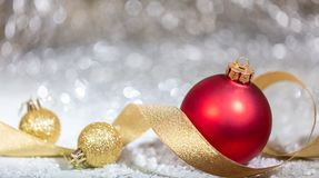 Christmas red ball, golden ribbon and snow, abstract bokeh lights background. Copy space royalty free stock photos