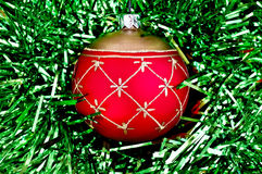 Christmas red ball on the green tinsel Royalty Free Stock Photography
