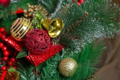 A Christmas red ball hangs on the background of a clock. It`s time for a new year. Multicolored glare and brilliance royalty free stock photography
