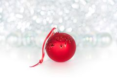 Christmas red ball on red ribbon on background of shiny tinsel, white bolls, lights and sparkles bokeh close up stock image