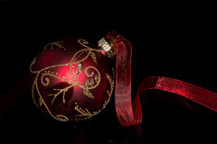 Christmas Red. Christmas ball with red ribbon on black background Stock Photography