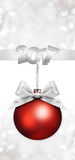 Christmas red ball with silver satin ribbon bow. On silver blurred lights background Stock Images