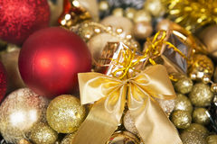 Christmas red balls and bow on gold background. Royalty Free Stock Photo