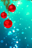 Christmas red balls with green fir tree on colorful blue bokeh Stock Photo