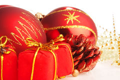 Christmas red balls, tiny present boxes and a cone Stock Images
