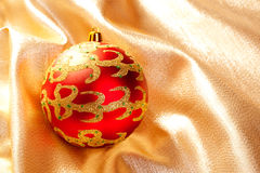 Christmas red bauble on golden  fabric Royalty Free Stock Photo