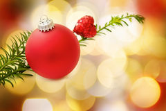 Christmas red bauble and heart. Christmas love and magic with festive red bauble and traditional pine tree branch over defocused fairy lights stock photography