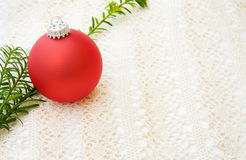 Christmas red bauble over lace. Celebrating Christmas with festive red bauble and traditional pine tree branch. Over handmade old lace stock photography