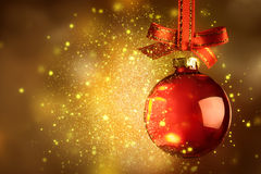 Christmas red bauble with sparkle over magic glitter shiny backg Royalty Free Stock Images