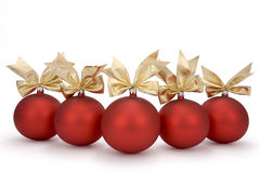 Christmas red baubles. With ornamental ribbon (bow) arranged abreast on white background. Clipping path incl Royalty Free Stock Photo