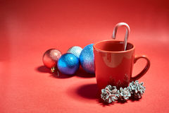 Christmas red bowl with pine cones and Christmas toys on a red background Royalty Free Stock Images
