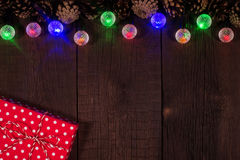 Christmas red box with garlands on a wooden background. Stock Image