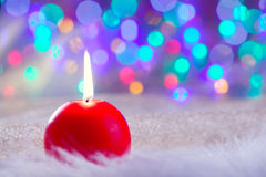 Christmas red candle on fur and colorful light Stock Photo