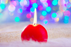 Christmas red candle on fur and colorful light Stock Images