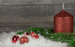 Christmas red candle in the snow with Christmas balls Royalty Free Stock Images