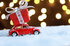 Christmas red car with gift box on snow. Happy New Year`s card stock photo