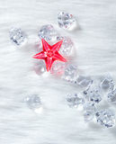Christmas red crystal star on ice cubes and fur Royalty Free Stock Photography