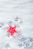 Christmas red crystal star on ice cubes and fur Stock Photo