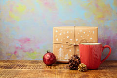 Christmas red cup with gift and decorations on wooden table over artistic background Stock Image