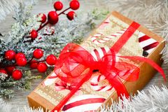 Christmas. Red Christmas flower packed gift and snow fir tree. on traditional white wood background Royalty Free Stock Image