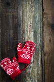 Christmas Red Knitted Mittens with Snowflake Motives. On rustic wooden background stock photography