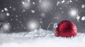 Christmas red Luxury ball in snow and abstract snowy atmosphere stock image