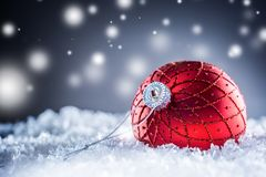 Christmas red Luxury ball in snow and abstract snowy atmosphere royalty free stock photo