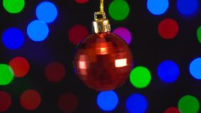 Christmas red mirror ball toy is spinning close-up. Decor with new year tree lights twinkling. Christmas red mirror ball toy is spinning close-up. Decor with stock video