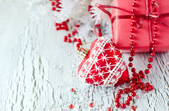 Christmas red present box with a heart decoration copy space. Greeting card for xmas on white wooden background Stock Image